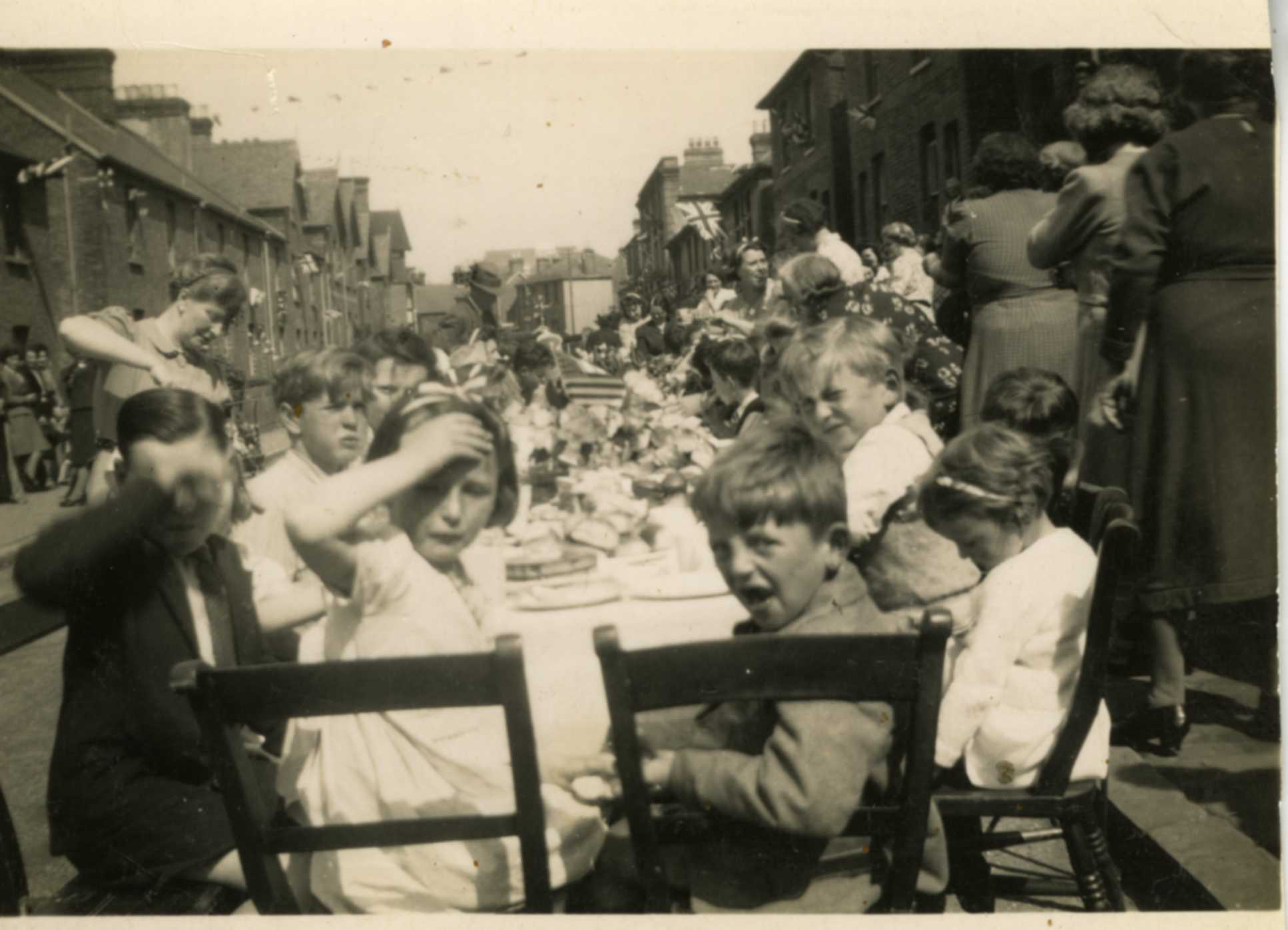 A black and white photograph with children seated at a table.
