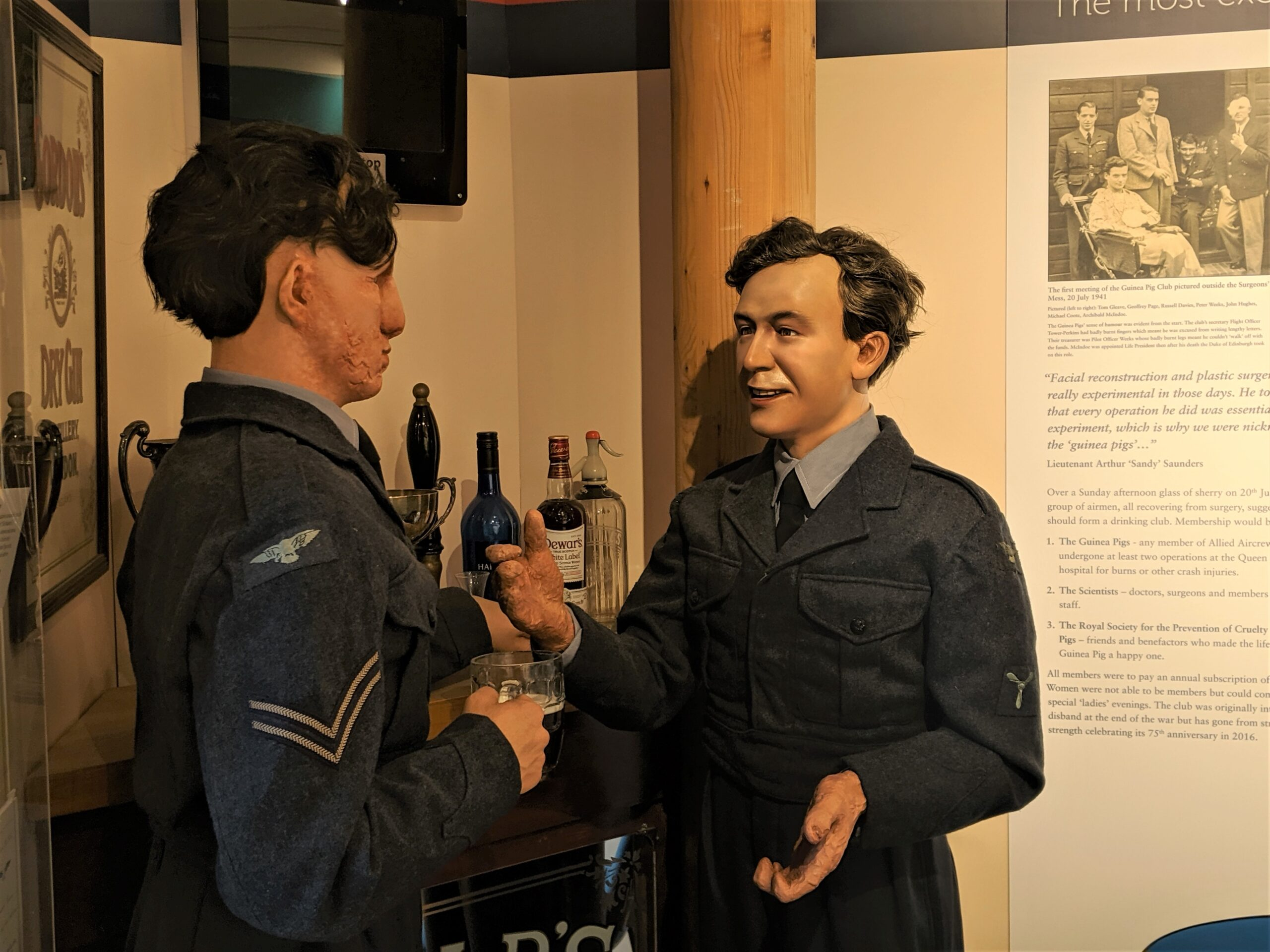 Guinea Pig Club manniquins, dressed in dark blue RAF uniforms standing at a bar